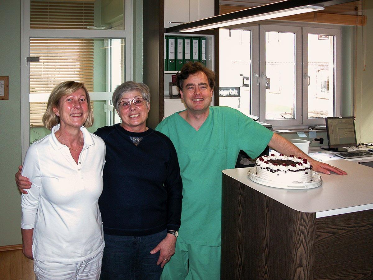Zahnarzt Dr. Born und Mitarbeiterin mit Patientin und Schwarzwälder Kirschtorte